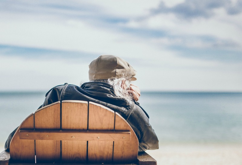 elderly man on the beach sitting in a wooden chair
