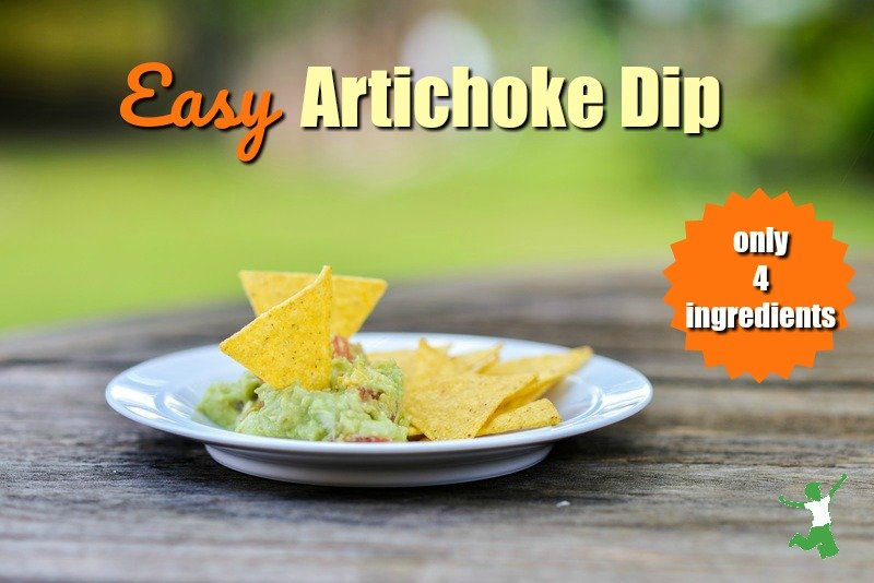 homemade artichoke dip on a white plate with tortilla chips