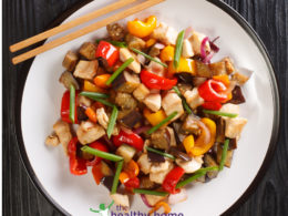 teriyaki chicken and roast vegetables on a white plate with chop sticks
