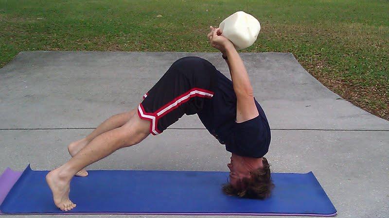man in yoga pose balancing a gallon of raw milk