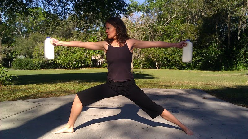 Woman holding two half gallons of raw milk in warrior 2 yoga pose