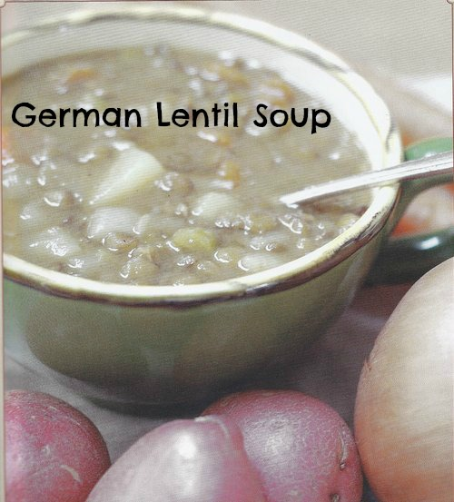 german lentil soup in a mug with potatoes on a table