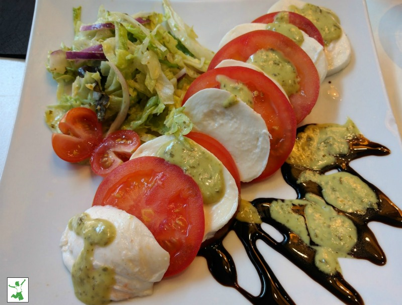 Caprese salad drizzled with balsamic on a white plate