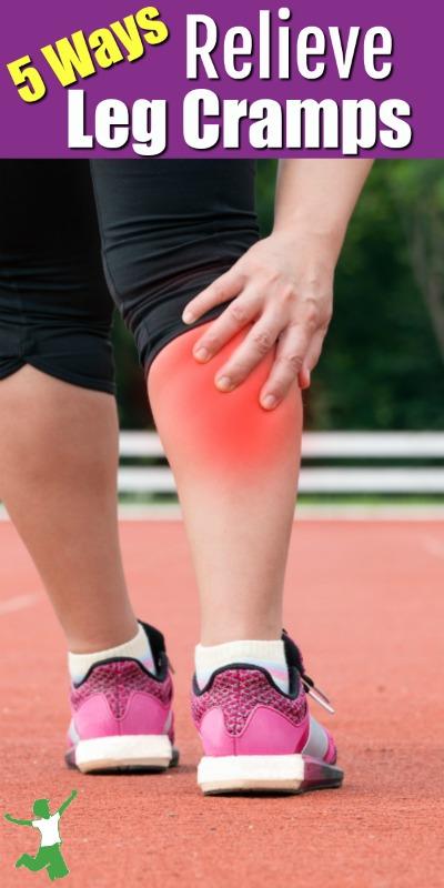woman grabbing her cramping leg in pain
