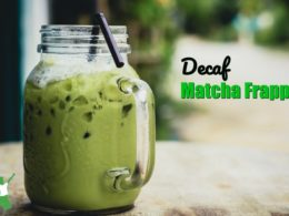 decaf matcha frappe in a mason jar mug with a straw on a wooden table