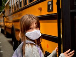 child wearing a mask boarding a school bus