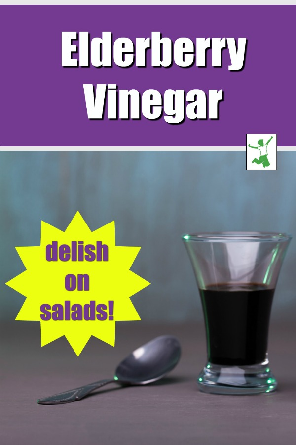 small glass of elderberry vinegar with a spoon