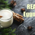 traditional eggnog in a glass with a cinnamon stick