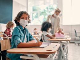 child wearing mask at school desk