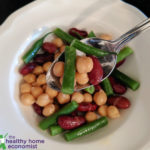 three bean salad in a white bowl with spoon