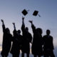 group of college graduates tossing their caps