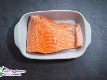 salmon fillet in a white baking dish