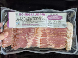 woman holding package of sugar-free bacon